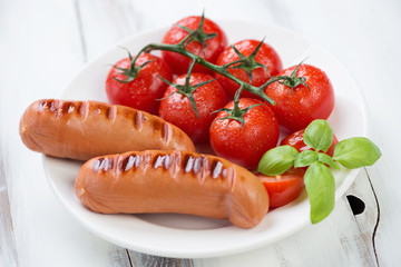 Grilled sausages with roasted red tomatoes and green basil