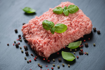 Raw ground meat with spices over black wooden background