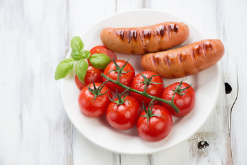 Grilled sausages and fried red tomatoes on a branch, above view