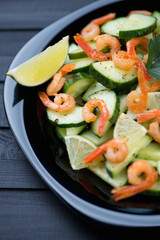 Salad with shrimps, cucumbers and lime in a glass plate
