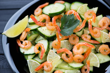 Close-up of salad with roasted shrimps, sliced cucumber and lime