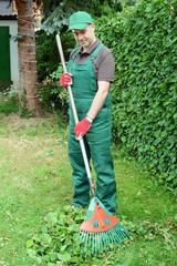 Gärtner arbeitet mit Rechen im Garten