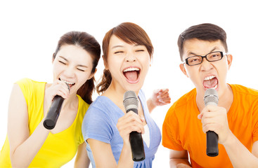 happy young group having fun singing with karaoke