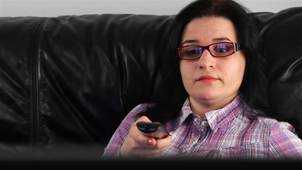 Young woman with remote control watching boring movie