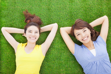 two happy young woman resting on grass