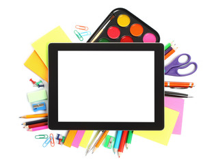 Tablet PC with school office supplies on white background.