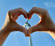 Heart from hands with a wind turbine in the background
