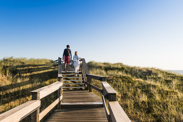 People on wooden footpath on dune on the  beach in Germany.