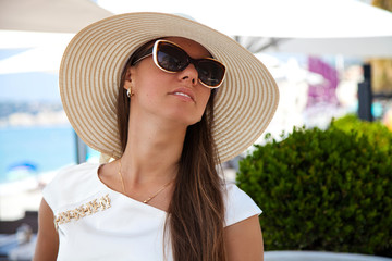 Beautiful young woman in elegant hat and sunglasses