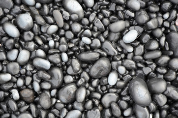 Black lava pebbles on beach