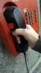 Old red public telephone with black handset and male hand