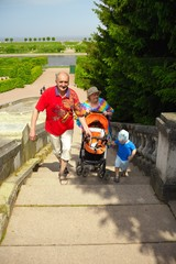 Grandmother, grandfather and grandson walk upstairs with stoller