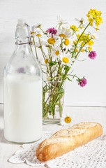 Fresh milk in old fashioned bottle with baguette
