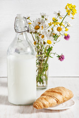 Fresh milk in old fashioned bottle with croissant