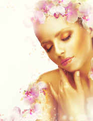 Beauty. Woman with Perfect Bronzed Skin and Orchid Flowers