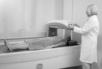 Woman in 40s undergoing exam in Bone Densitometer machine with m