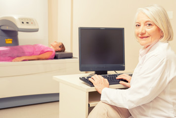 Mature woman doctor analyzing woman in 40s at bone densitometer