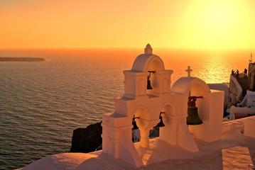 Church bells of Santorini Greece overlooking the sea at sunset