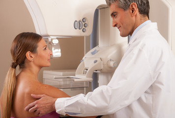 Young male doctor reassuring woman before mammography scan