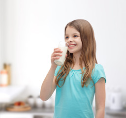 smiling little girl drinking milk out of glass