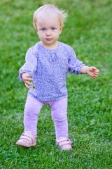 Funny cute baby girl on grass