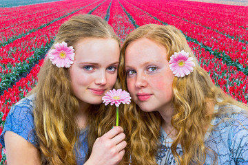 Two teenage girls in front of red tulip field