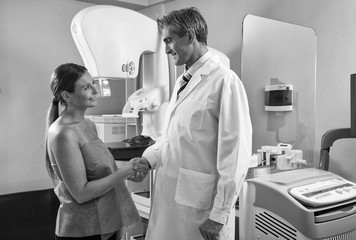 Happy smiling male doctor and woman patient shaking hands after