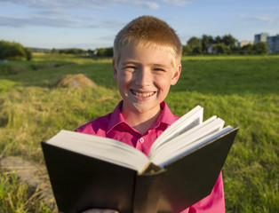 The boy reads the book outdoors