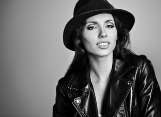 woman in leather jacket and hat, studio B/W shot.