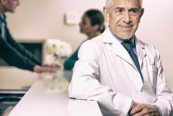 Smiling senior male doctor smiling at hospital reception desk, f