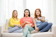three smiling teenage girl watching tv at home
