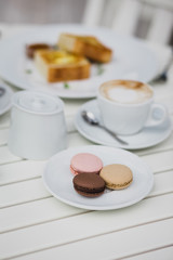 breakfast with cheesecakes, toast, cappuccino and macarons