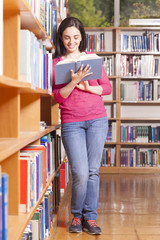 Smiling young student reading a book in a library