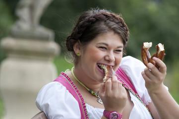 Oktoberfest Frau beim Brezel essen