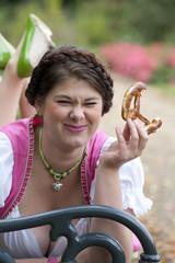 Oktoberfest Frau mit Dirndl beim Brezel essen
