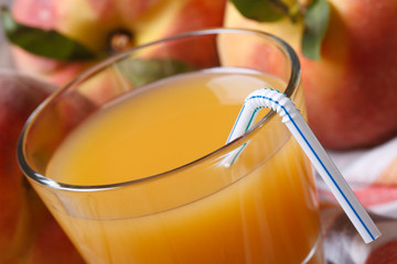 fresh peach juice in glass macro on a background of ripe fruit