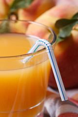 fresh peach juice in glass macro and ripe fruit. Vertical