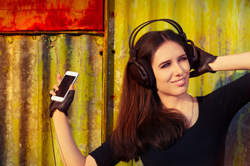 Girl with Big Headphones and Smart Phone on Grunge Background