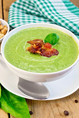 Soup puree with bacon and spoon on board