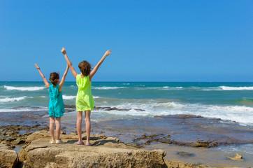 Happy kids on ocean beach having fun