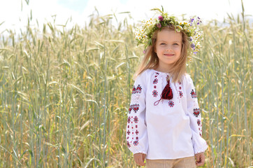 Smiling girl standing against wheat field background