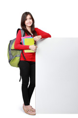 Young happy student carrying books with copyspace