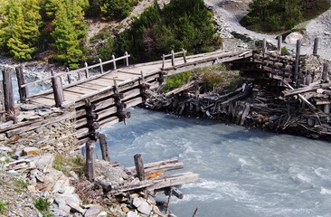 Wooden foot bridge over a glacial river, Himalayas, Nepal