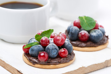 delicious mini cakes with chocolate cream and berries