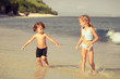 two happy kids playing on beach at the day time