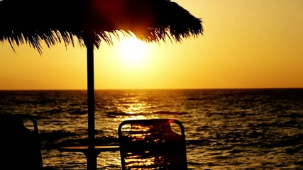 sunbed and parasol on the beach, sunset.