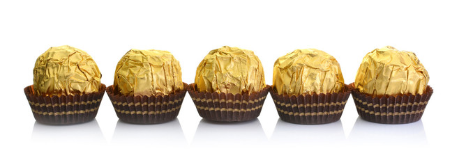 Chocolate ball with almond in a gold foil paper.