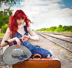 Woman with  suitcase on a train station.