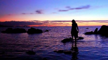 Silhouette of woman walking at a rocky beach, rises on stone