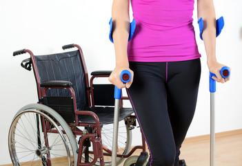 Frau mit Rollstuhl und Krücken